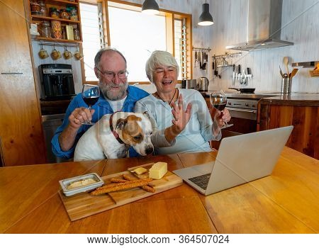 Covid-19 Stay Connected. Happy Senior Couple With Pet Dog And Wine Video Calling Friends On Laptop O