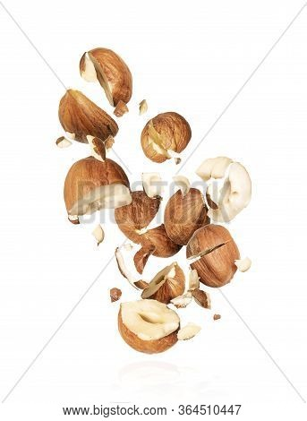 Randomly Frozen Crushed Hazelnuts In The Air On A White Background