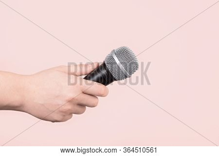 Hand Holding Up A Microphone Isolated Against A Pale Pink Background