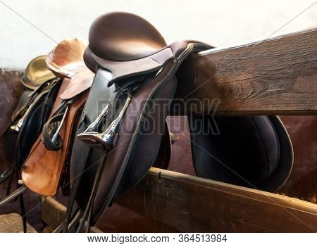 Leather Saddles Horse With Stirrups On A Back Of A Wooden Fence Stable