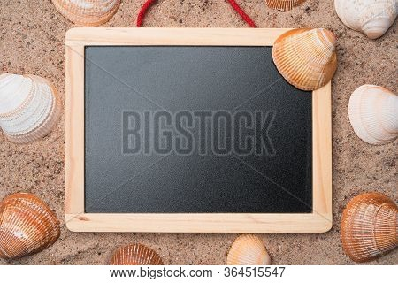 Blank Blackboard With Seashells On A Golden Beach Sand. Summer Travel Concept. Copy Space In The Cen