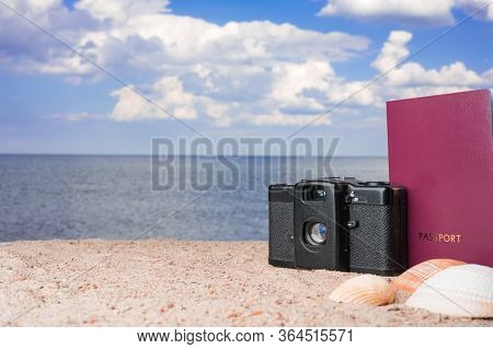 Passport, Vintage Film Camera And Seashells On Golden Beach Sand. Summer Travel Abstract Concept. Co