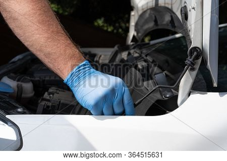 Caucasian Man In Protective Glove Opening Hood Or Bonnet Of A Car. Mechanic Repair Or Vehicle Mainte