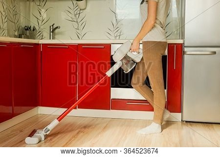 Woman Headless Cleaning House With Red Wireless Vacuum Cleaner. Red Kitchen, Quarantine Concept.
