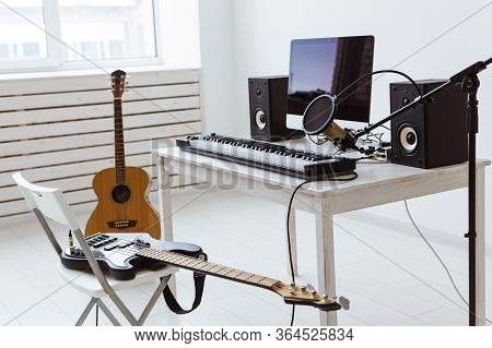 Microphone, Computer And Musical Equipment Guitars And Piano Background. Home Recording Studio Conce