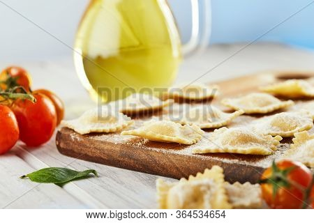 Tasty Raw Ravioli With Flour, Cherry Tomatoes, Sunflower Oil And Basil On A Light Wooden Background.