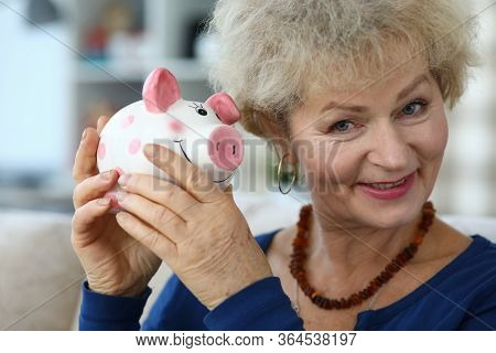 Portrait Of Senior Charming Woman Holding Piggy-bank. Elderly Female And Ceramic Container For Coins