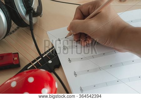 Music Instruments Concept Background. Close Up Musician Writing Note On The Paper For Create Song Wi