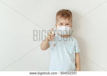 Boy In Medical Face Mask Hold Sanitiser Bottle. Caucasian Child Wearing Flu Protection Looking At Ca