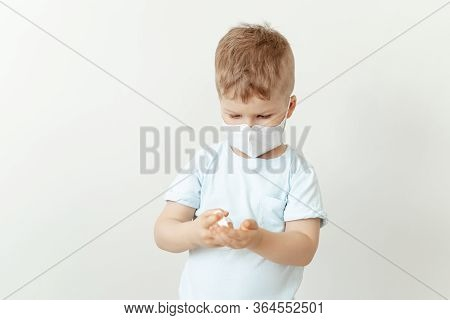 Little Boy In Medical Mask Using Sanitiser Bottle. Caucasian Kid Wearing Flu Face Protection. Busy C