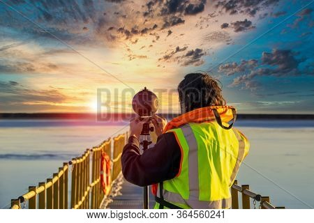 Young Caucasian male setting up a 360 view camera on the bridge with yellow handrails , on a lake