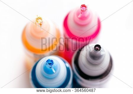 Four Open Printer Bottles With Cmyk Colour Ink. White Background. Shallow Depth Of Field
