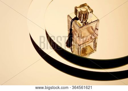 High Angle View Of Luxury Perfume Bottle On Round Mirror Surface With Reflection