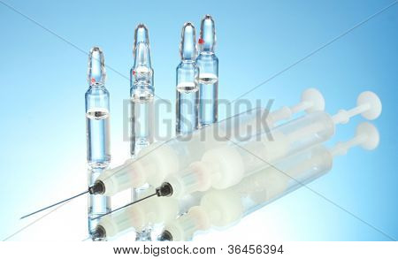 syringes monovet and ampoules on blue background