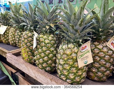 Orlando,fl/usa-5/3/20: A Row Of Fresh Dole Pineapples At A Whole Foods Grocery Store.