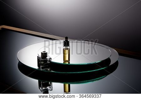 High Angle View Of Perfume Bottle And Serum Bottle On Grey Mirror Surface