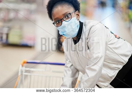 African Woman Wearing Disposable Medical Mask And Gloves Shopping In Supermarket During Coronavirus