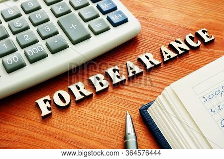 Forbearance Word From Small Wooden Letters And Calculator.