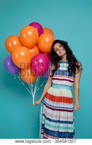 Smiling Carefree Curly Girl In Dress Holding Bright Colorful Air Balloons Isolated On Blue Backgroun