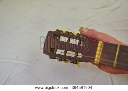 Fingers Turning The Tuning Pegs And Gears Of The Headstock Of An Acoustic Guitar. Tuning The Guitar.