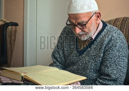 Elderly Turkish Muslim Male Reciting The Holy Book Of Islam, Qur'an In Ramadan