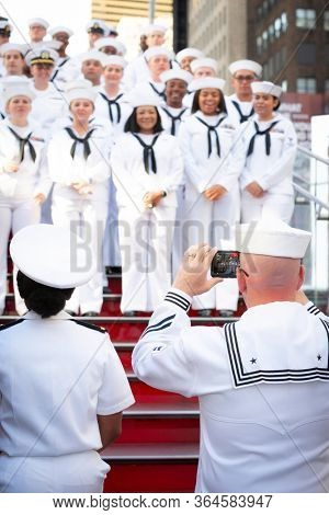 MAY 22 2019-NEW YORK: A sailor takes a cellphone of a group of Sailors on the iconic red steps in Father Duffy Square during Fleet Week in Manhattan on May 22, 2019.