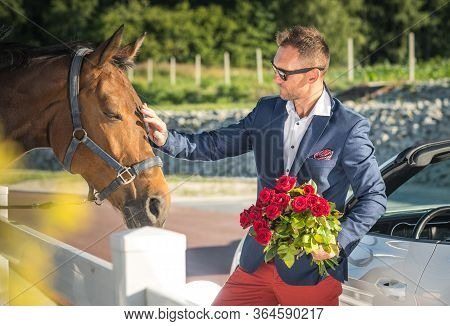 Wealthy Well Dressed Caucasian Man Holding Bouquet Of Red Roses And Petting Horse.