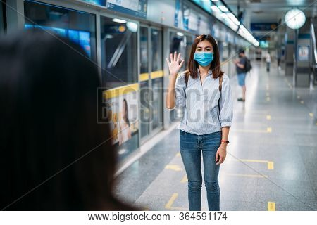 Two Young Asian Women Friends Wearing Protective Mask Meet In A Subway Station With Bare Hands. Inst
