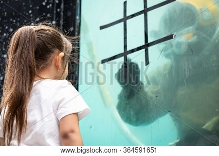MAY 24 2019-NEW YORK: A girl plays tic tac toe with a US Navy EOD technician on the glass of a 6,800 gallon mobile dive tank at the Military Island Plaza in Times Square, Fleet Week on May 24, 2019.