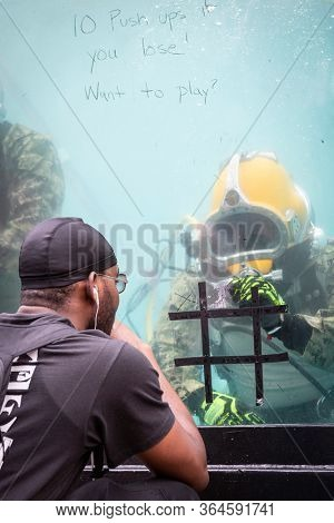 MAY 24 2019-NEW YORK: A man plays tic tac toe with a US Navy EOD technician on glass of a 6,800 gallon mobile dive tank at the Military Island Plaza in Times Square, Fleet Week on May 24, 2019.