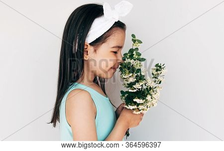 Side View Image Of Beautiful Child Smelling The Bouquet Of White Flowers. Cute Kid Rewceived A Bouqu