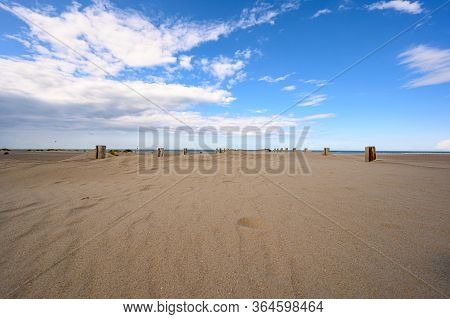 The Beach At Dunkirk With Wooden Poles Of The Sea Defences And White Clouds In A Blue Sky.