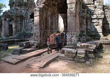Siem Reap, Cambodia - February 15, 2020: Cambodian People Carrying A Giant Sandstone During The Reno