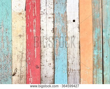 Texture of vintage wood boards with cracked paint of white, red, orange, yellow, cyan and blue color. Retro background with old wooden planks of different colors