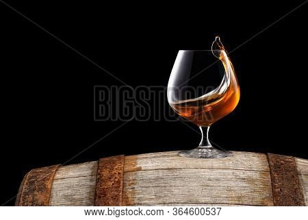 Brandy Or Cognac In Snifter Glass With Wave Surface Level On Old Wooden Barrel As Table Isolated On