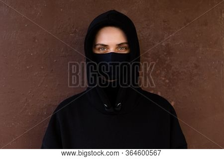 Young Woman Wearing Face Mask. Handsome Woman In Black Hoodie Wear Black Medical Mask. Pandemic Coro