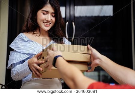 Portrait Of Happy Smiling Asian Woman In Casual Clothing Receiving A Pizza Packaging Box From Delive