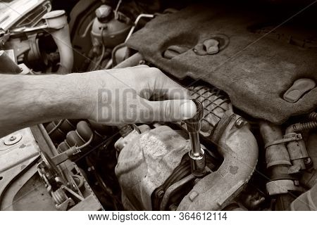 Mechanic Checking And Fixing A Broken Car In Car Service In B/w