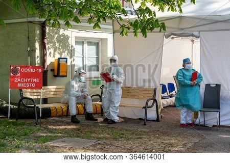 Ruzomberok, Slovakia - May 4, 2020: Doctors In Protective Suits And Shields In Front Of Tent Waiting
