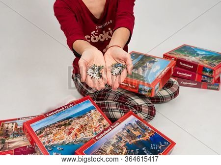 Kiev, Ukraine April 11 2020 : Cheerful Young Woman Putting Jigsaw Puzzle Pieces During Quarantine. M