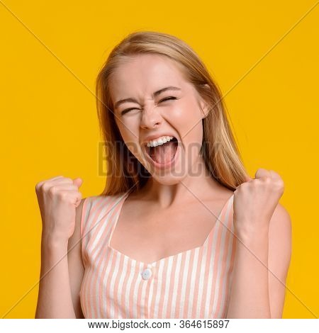 Crazy Sales. Pretty Young Girl Emotionally Shouting With Raised Fists, Celebrating Success Over Yell