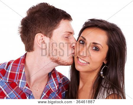 Close-up of a red-haired young man kissing his girlfriend on her cheek