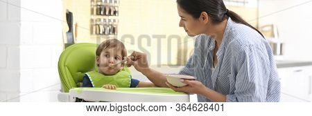 Young Nanny Feeding Cute Little Baby In Kitchen. Banner Design