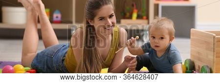 Teen Nanny And Cute Little Baby Playing With Xylophone At Home. Banner Design