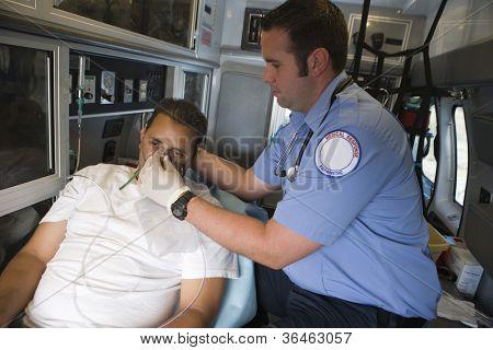 Male EMT professional helping man with oxygen mask inside ambulance