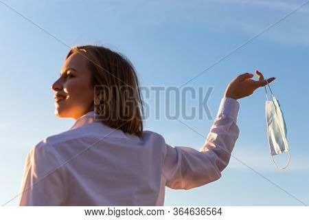 Happy Woman Takes Off Medical Protective Mask Holds It On Her Finger On Blue Sky Background, Enjoys