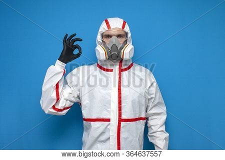 Professional Disinfector Man In Protective Suit Shows Okay Sign On Blue Isolated Background, Disinfe