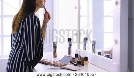 Beauty Woman Applying Makeup. Beautiful Girl Looking In The Mirror And Applying Cosmetic With A Big