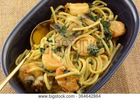 Closeup Of Shrimp And Pasta Dinner With Spinach And Mushrooms In Light Cream Sauce In Blue Serving B