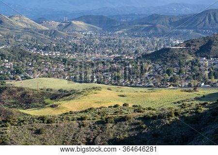 Grassy meadows at Santa Monica Mountains National Recreation Area and Newbury Park homes and streets. in Ventura County, California.